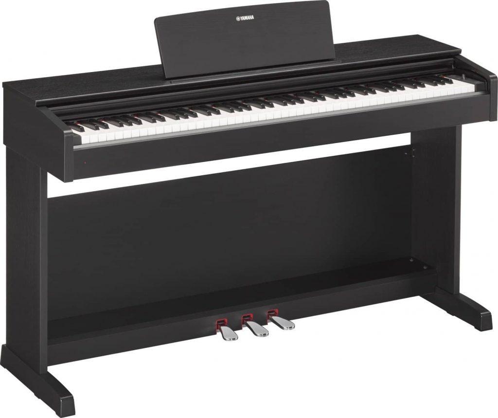 Un piano droit numérique non portable avec les trois pédales d'un piano à queue acoustique